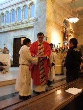 El Padre Joe Fugolo recibiendo las ofrendas de la gente para la Eucaristía.