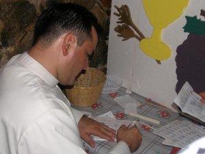 P. Fernando firma la boleta de los niños de la catequesis.