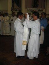 El Padre Miguel Ángel reviste al Padre Héctor de los ornamentos sacros.