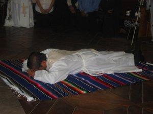 ... mientras Héctor se postra en tierra, como signo de hacerse siervo de todos, como Cristo que se humilló hasta la muerte.