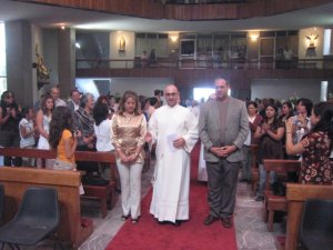 y el candidato, junto con su hermano y su madrina hacen su entrada para su ordenación
