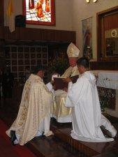El Señor Cardenal le entrega al Padre Mauro la patena con el pan y el caliz con el vino.