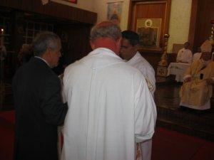 El Padre Román ayuda al Padre Mauro a revestirse de la Estola y la Casulla.