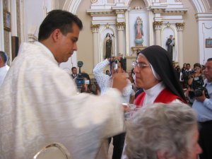 Padre Lino da la Comunión a su hermana Religiosa, Sor María Leticia, de las Adoratrices Perpetuas del Santísimo Sacramento.