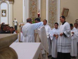 El Padre Conrado Fernández, Padrino de Lino, lo reviste con la estola y la casulla.