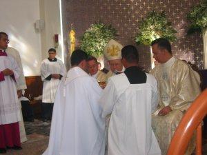 El Señor Obispo entrega al Padre Tomás el cáliz con el vino y la patena con el pan.