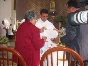 La Madre y el Hermano mayor del Padre Tomás lo ayudan a limpiarse las manos del santo crisma.