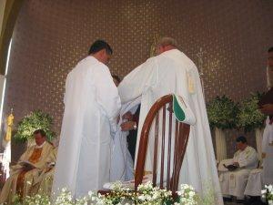 El Padre Román, Padrino del Padre Tomás, ayuda a su ahijado a revestirse con la estola y la casulla.