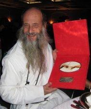 El premio consiste en una placa de plata con la imagen de las manos de la creación de Miguel Angel.  Pintura que adorna la capilla sixtina en el Vaticano.<br />