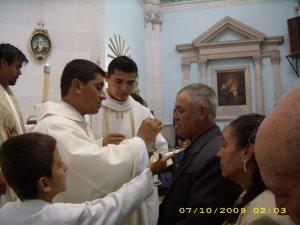P. Juan Luis dando la comunión a su papá.